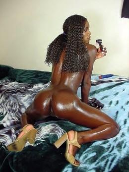 Oiled jet-black girl posing very..
